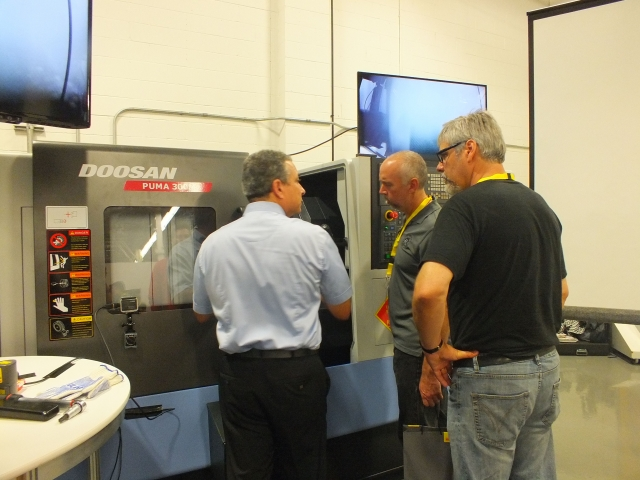 Attendees speak with John Benedetti of Sandvik Coromant about the company's PrimeTurning technology, which was showcased on the Doosan Puma CNC lathe at Ferro Technique