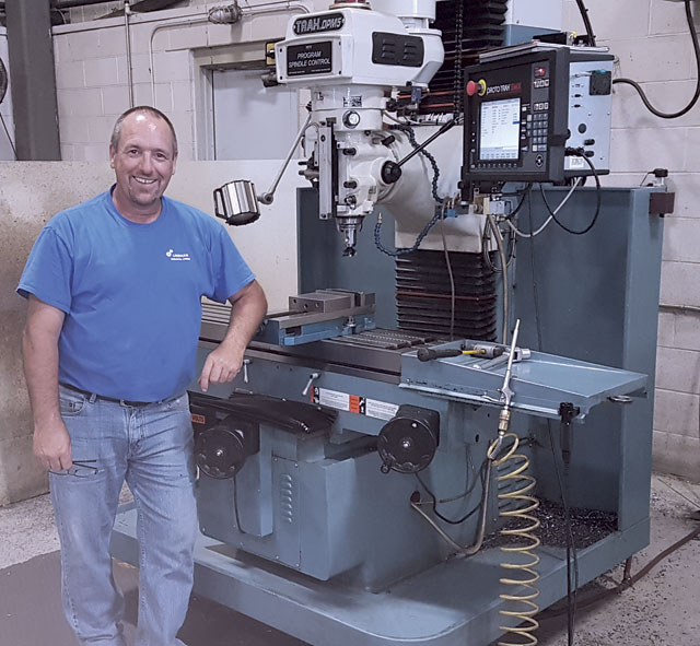 Lindham Industries co-owner Marc Lapointe standing alongside one of his TRAK combo mills.