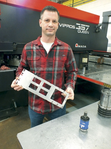 Bayview Metals' Derek Richardson with a part punched out on an Amada machine using Wilson Tool punch tooling.