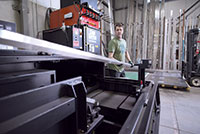 Jody Seufert, one of Reggin Industries machine operators, loads material onto the Amada ENSIS RI for processing.