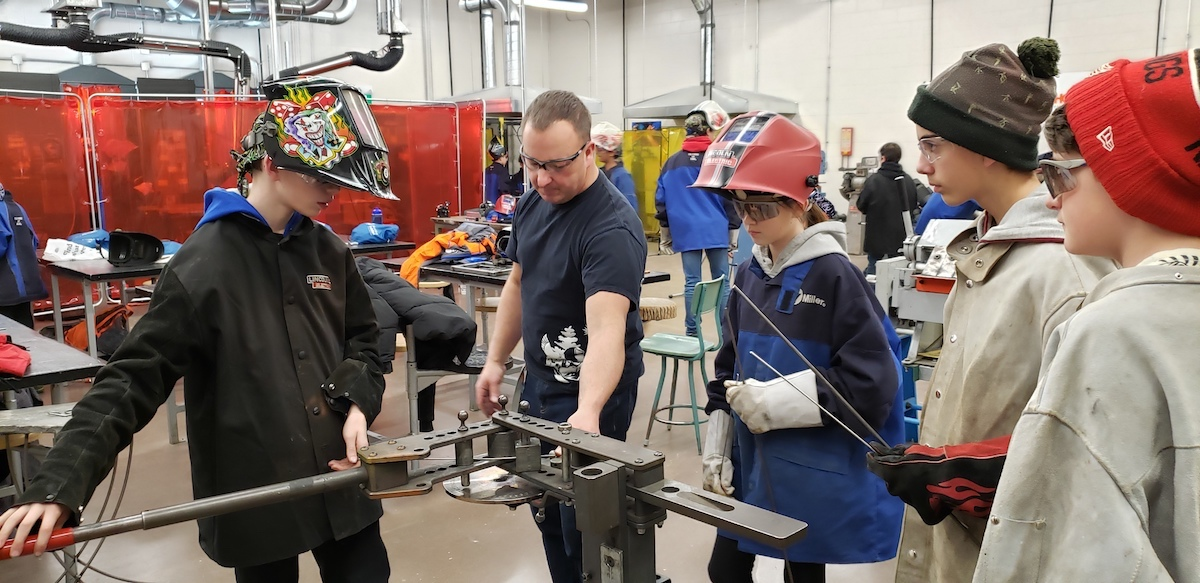 Richard Alexander shows students how to bend a welding rod