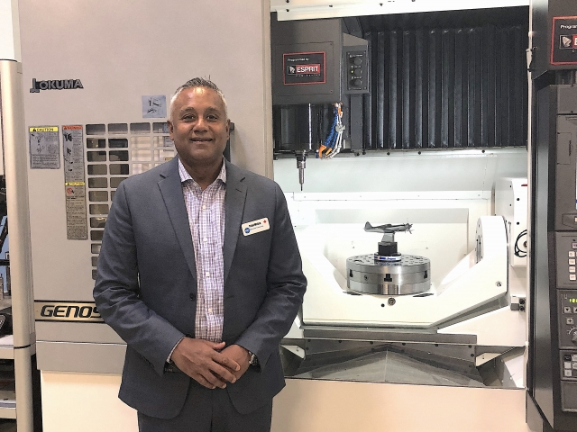 Tejal Mehta, vice president of operations, EMEC Machine Tools, beside the Okuma M460V-5AX that was under power during the open house.