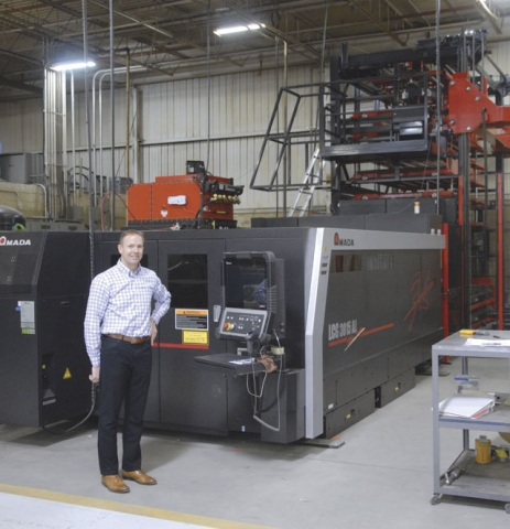 Jeff Nelson beside the newly purchased Amada LCG3015 AJ fiber laser cutter with the automatic feeder in the background.