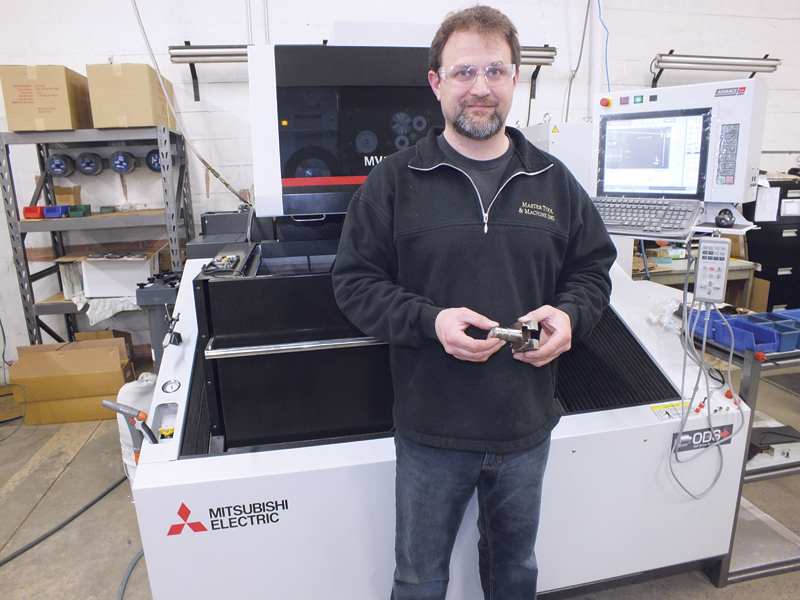 Mathew Stoer with a part machined on the new wire EDM. Stoer continues to find new uses for the EDM, and is considering the purchase of a second one.