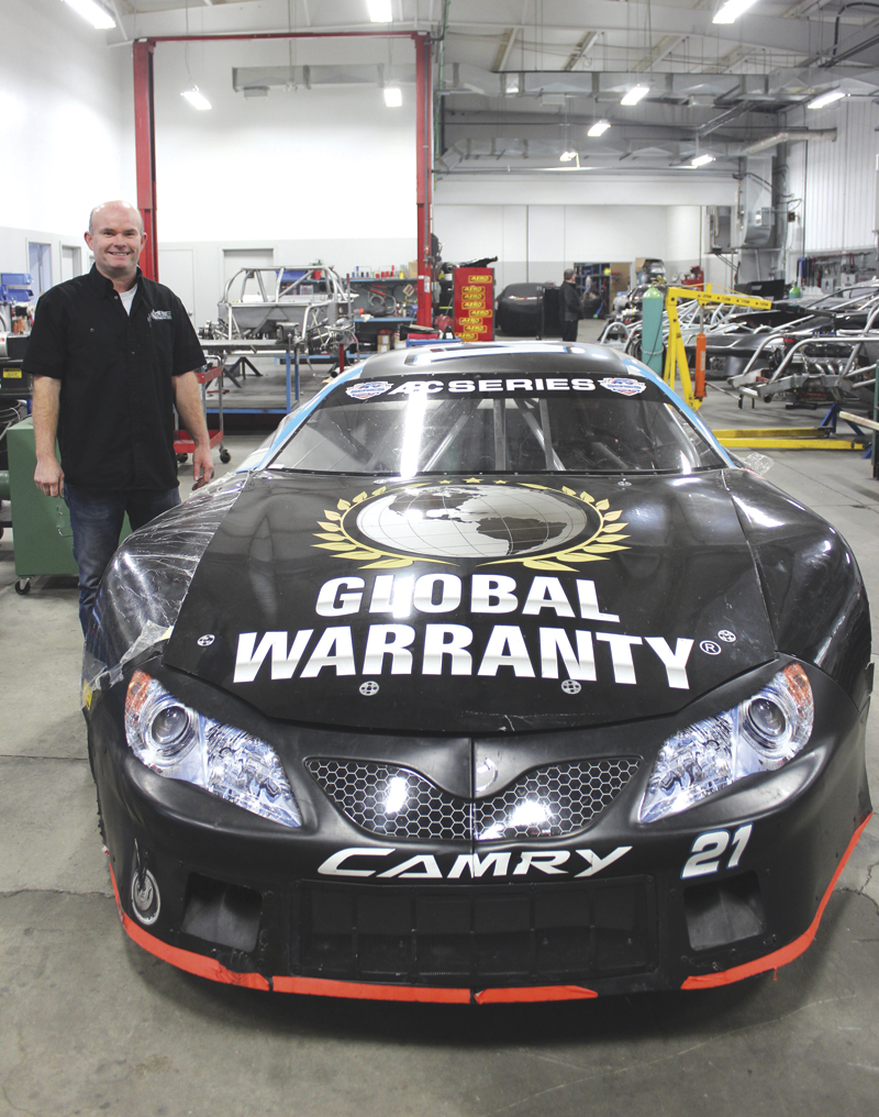 Mike McColl poses by a Camry racecar welded and finished in his shop.