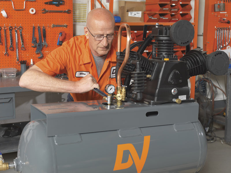 Mike Schoneveld completes the assembly of DV Systems' finished air compressor unit.
