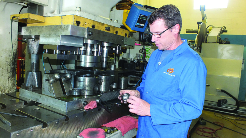 Joseph Tielemans examines a faucet component stamped on the larger Komatsu, the H1F 150 ton stamping press.