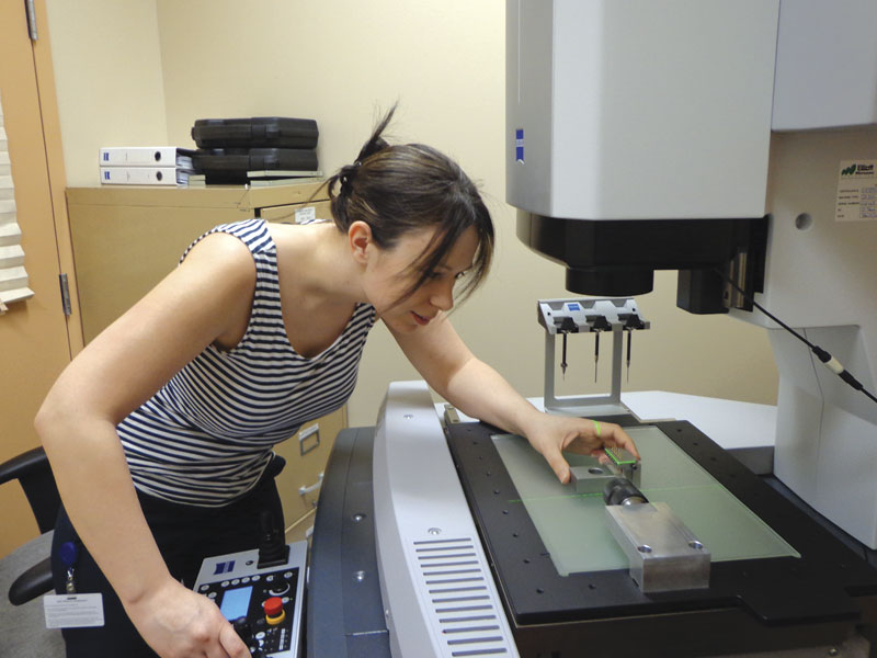 Sheila Selby, CMM programmer at Amphenol Canada Corp., aligns a fixture to the laser location on the Zeiss multi-sensor machine.